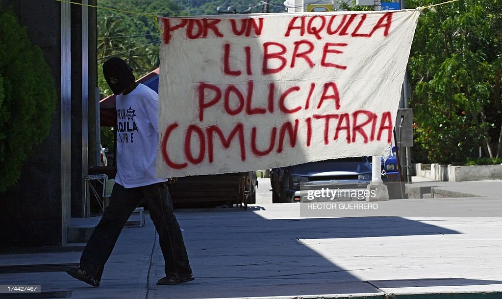 A masked and armed resident --member of the new community police group-- walks in front of a poster reading 'For a free Aquila. Community Police' at the main square in Aquila, Michoacan State, Mexico on July 25, 2013. This new group of armed residents settled in recent days to protect the community from organized crime. AFP PHOTO/Hector Guerrero