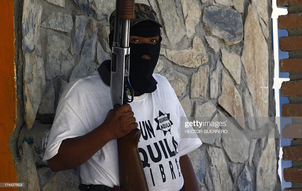 A masked and armed resident --member of the new community police group-- stands guard in Aquila, Michoacan State, Mexico on July 25, 2013. This new group of armed residents settled in recent days to protect the community from organized crime. AFP PHOTO/Hector Guerrero
