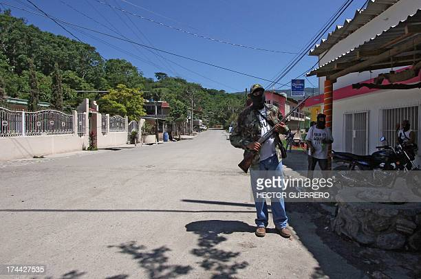 Masked and armed residents members of the new community police group stand guard in Aquila Michoacan State Mexico on July 25 2013 This new group of...