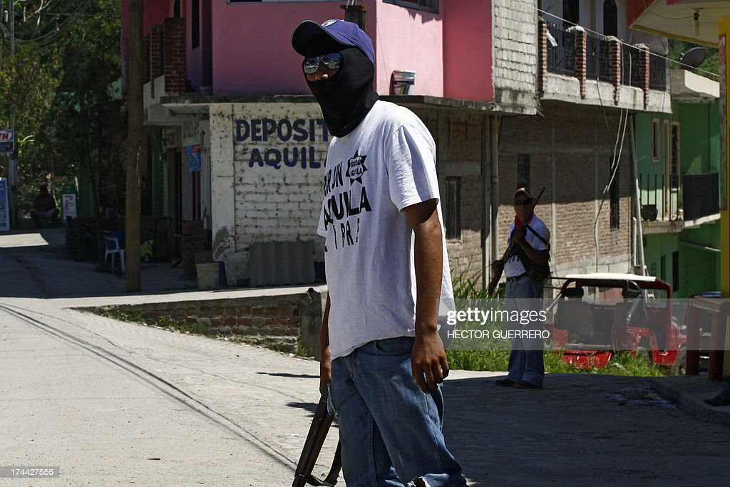 Masked and armed residents --members of the new community police group-- stand guard in Aquila, Michoacan State, Mexico on July 25, 2013. This new group of armed residents settled in recent days to protect the community from organized crime. AFP PHOTO/Hector Guerrero