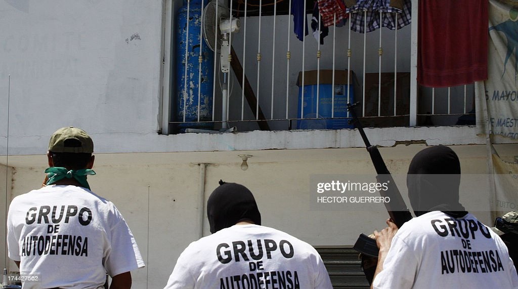 Masked and armed residents --members of the new community police group-- wear T-shirts reading 'Group of self-defense' as they stand guard in Aquila, Michoacan State, Mexico on July 25, 2013. This new group of armed residents settled in recent days to protect the community from organized crime. AFP PHOTO/Hector Guerrero