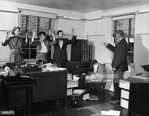 A masked and armed robber holds the staff of an office at gunpoint while his accomplice searches through files 1940s