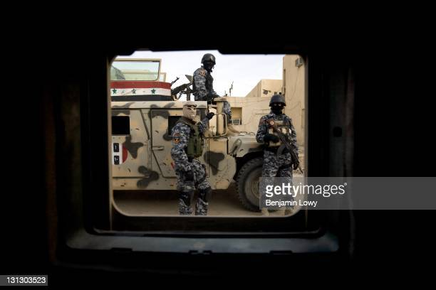 A masked and heavily armed Iraqi Army commando team stand by their vehicles and watch a passing mixed Iraqi and American military convoy on March 16...