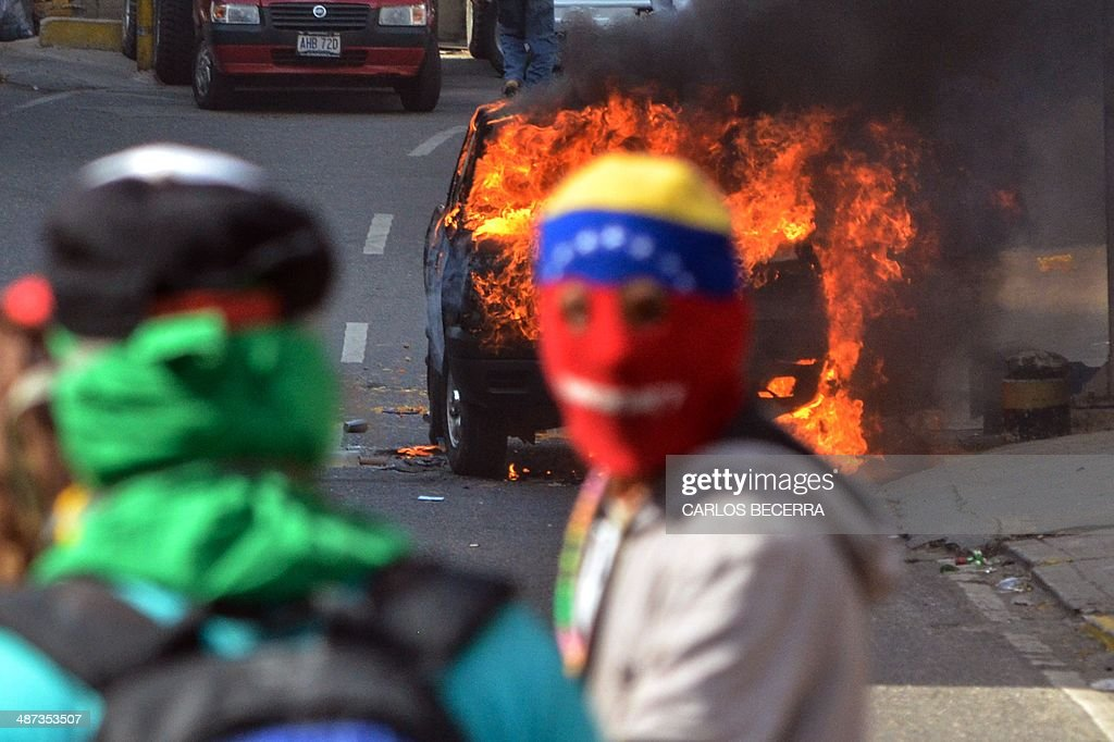 Masked anti-government activists burn a National Guard truck during a protest in Caracas April 29, 2014. AFP PHOTO/Carlos Becerra