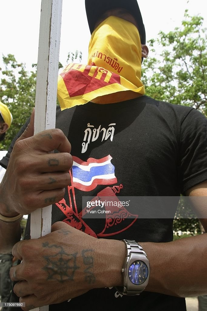 A masked antigovernment protestor with the word love tatooed onto his hands stands guard outside the police headquarters in downtown Bangkok About a...