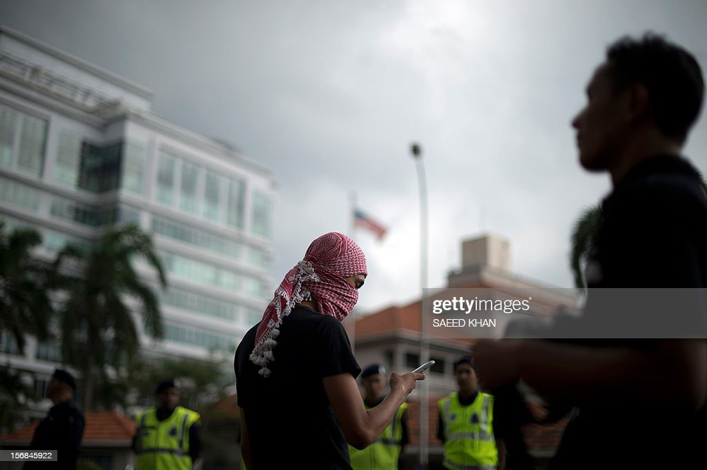 A masked anti-Israel protestor makes a call on his mobile phone in front of the US embassy during a protest in Kuala Lumpur on November 23, 2012. Dozens of students after offering their Friday prayers marched towards the US embassy while holding placards and banners to condemn Israel military aggression in Gaza and demanded the US be sincere in its efforts in the crisis. AFP PHOTO / Saeed KHAN
