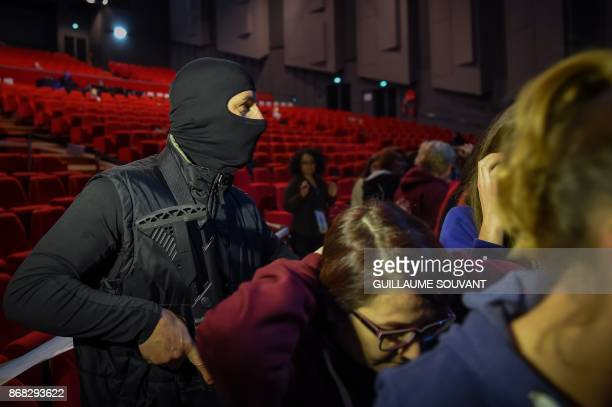A masked assailant gathers the hostages during an exercise simulating a terrorist attack inside the theatre Espace Malraux in JouelesTours central...