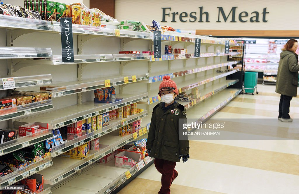 A masked boy walks past nearly empty shelves at a supermarket in the northwestern city of Akita on March 15, 2011 as panic buying sweeps the country following the March 11 earthquake and tsunami in eastern Japan as well as a nuclear crisis in Fukushima prefecture. Japan's nuclear crisis escalated on March 15 as two more blasts and a fire rocked the quake-stricken atomic power plant, sending radiation up to dangerous levels. AFP PHOTO / ROSLAN RAHMAN