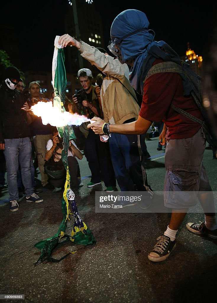 A masked demonstrator burns a Brazilian flag at a protest against the upcoming 2014 World Cup on May 15, 2014 in Rio de Janeiro, Brazil. Anti-World Cup demonstrations were held across the country today.