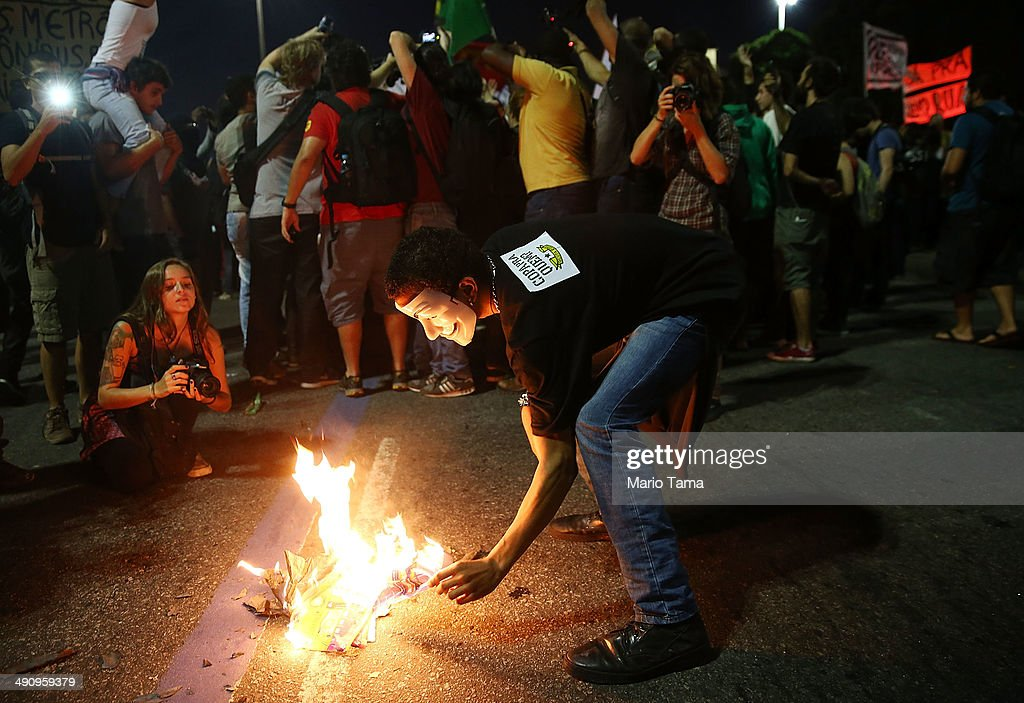 A masked demonstrator burns World Cup memorabilia at a protest against the upcoming 2014 World Cup on May 15, 2014 in Rio de Janeiro, Brazil. Anti-World Cup demonstrations were held across the country today.