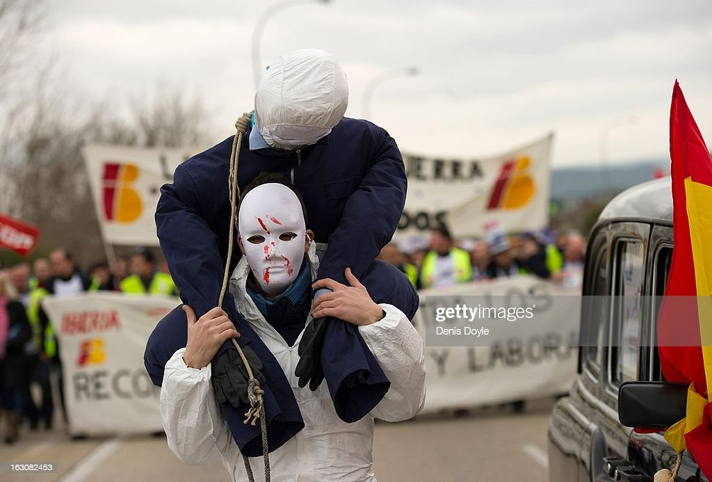 A masked demonstrator carries an effigy representing an Iberia worker during the march near Barajas Airport on March 4, 2013 in Madrid, Spain. Iberia workers have begun the second round of five day strikes in protest at plans by holding company IAG (International Consolidated Airlines Group), formed by the 2011 merger of Iberia and British Airways, to implement redundancies and pay cuts across the troubled Spanish airline. The strike is estimated to cause the cancelling of almost 1,300 flights this week, with a final round of five day strikes planned for March 18 to 22.