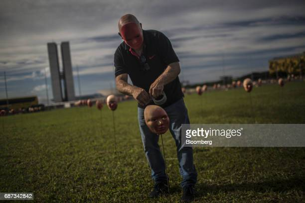 A masked demonstrator places a red mask in the ground part of the activist group Rio de Paz's art installation of masks symbolizing Brazil's...