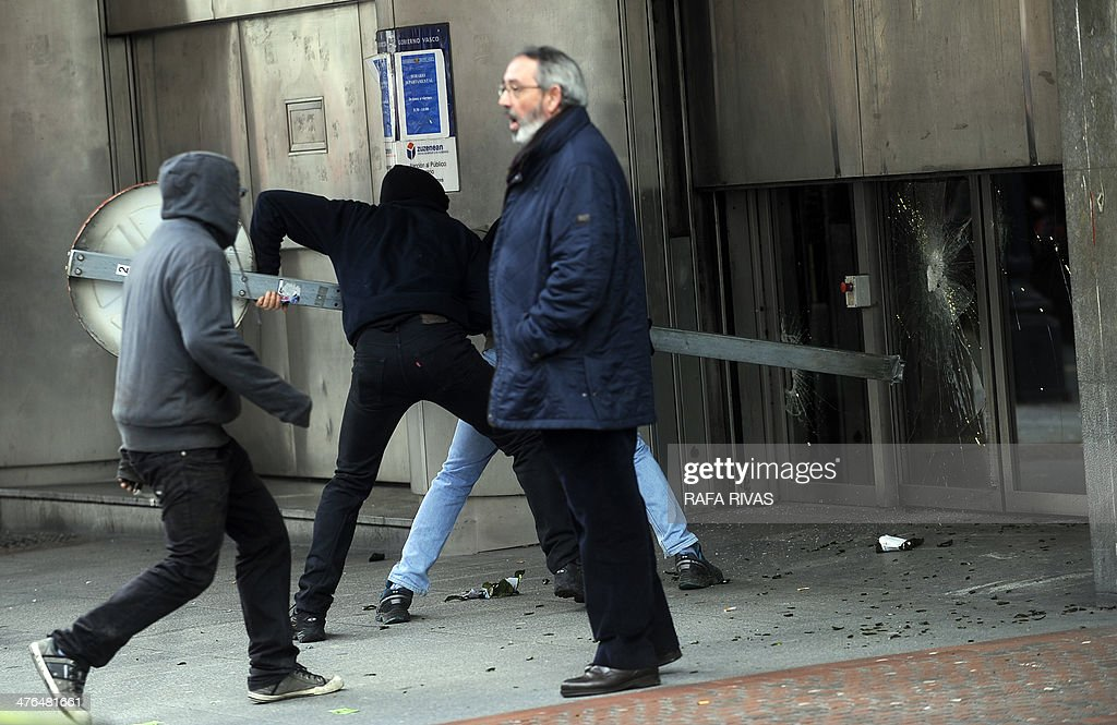 Masked demonstrators attack Basque Government's headquarters as a man protests in the northern Spanish Basque city of Bilbao during a demonstration against the celebration of the Global Forum Spain in Bilbao on March 3, 2014.