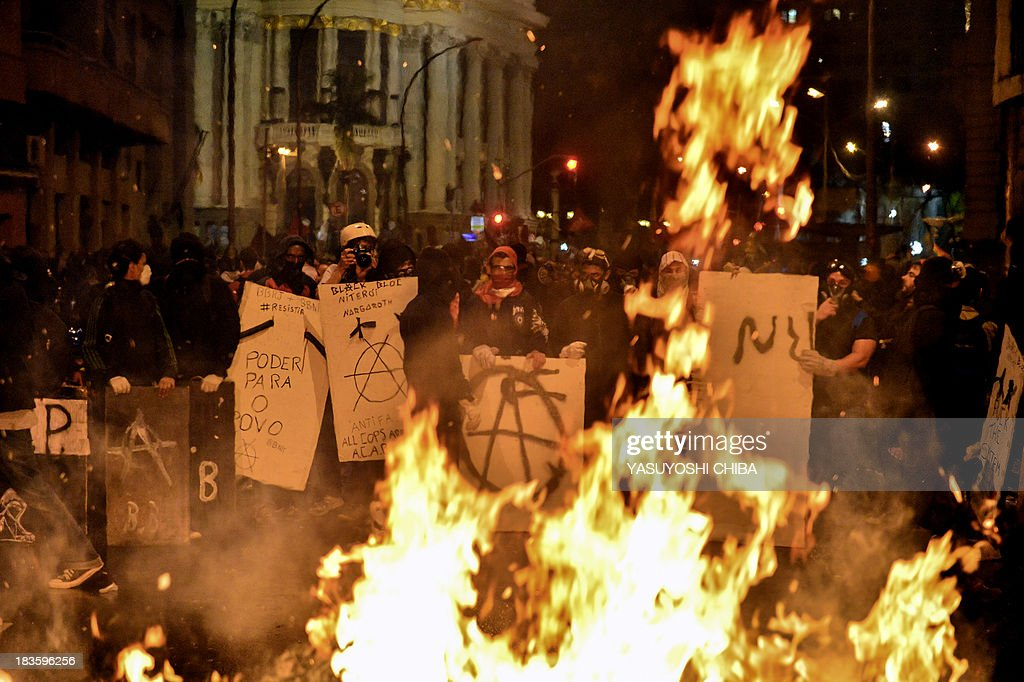 Masked demonstrators burn trash outside the City Hall, following a peaceful teachers protest demanding better working conditions and against police beating, on October 7, 2013 in Rio de Janeiro, Brazil.