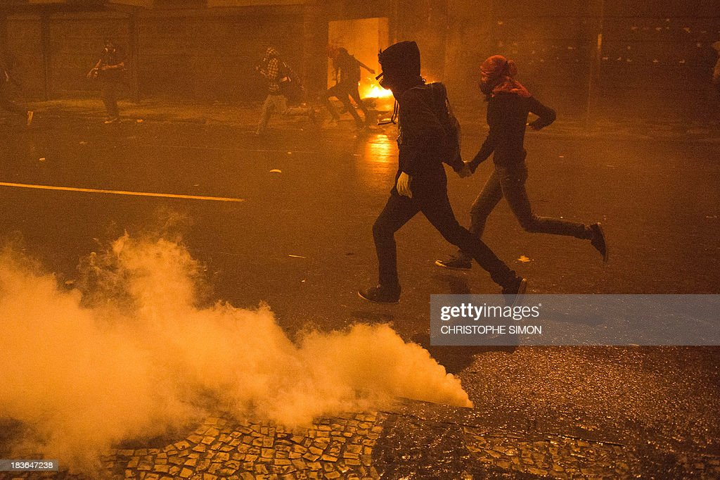 Masked demonstrators run for cover during clashes with police at the end of a teachers' protest demanding better working conditions and against police violence, on October 7, 2013 in Rio de Janeiro. AFP PHOTO / CHRISTOPHE SIMON