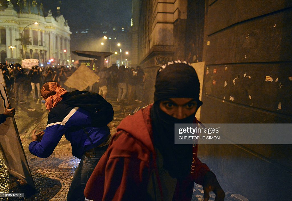Masked demonstrators throw molotov cocktails at the town's City Hall, following a peaceful teachers protest demanding better working conditions and against police beating, on October 7, 2013 in Rio de Janeiro.