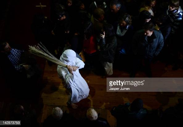 A masked flagellant lashes himselve inside la iglesia de Santa Maria La Mayor during the 'Los Picaos' Easter Week brotherhood procession on April 5...