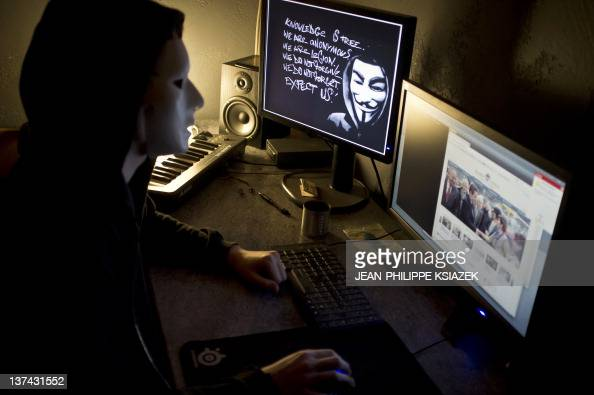 A masked hacker part of the Anonymous group hacks the French presidential Elysee Palace website on January 20 2012 near the eastern city of Lyon...