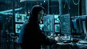 Masked Hacktivist Organizes Massive Data Breach Attack on Corporate Servers. He is in Underground Secret Location Surrounded by Displays and Cables.