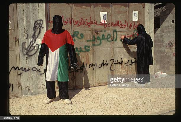 Masked Hamas members spray paint protest graffiti for a