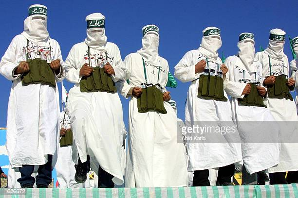 Masked Hamas militants dressed as suicide bombers march in a rally at the Khan Younis refugee camp December 13 2002 in Khan Younis in southern Gaza...