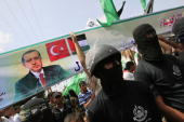 Masked Hamas militants hold a banner bearing the portrait of Turkish Prime Minister Recep Tayyip Erdogan and the Turkish and Palestinian flags during...