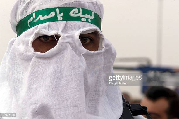 Masked Iraqi men march during a parade in Mosul north of Baghdad February 4 2003 Thousands of armed volunteers paraded in northern Iraq in defiance...