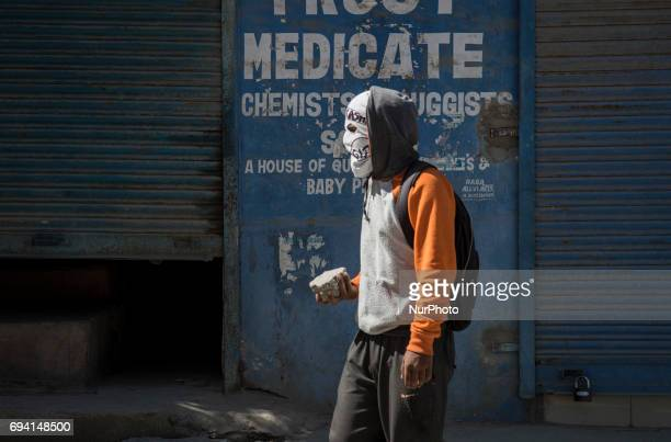 A masked Kashmiri holds a stone before throwing it at Indian policemen during a protest Friday June 9 in Srinagar Indianadministered Kashmir India...