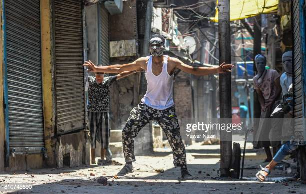 A masked Kashmiri Muslim protester taunts Indian government forces during a protest after they defied curfew on the the first death anniversary of...