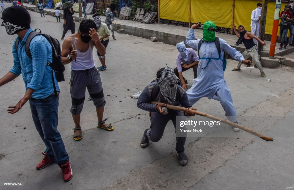 Masked Kashmiri Muslim protester throws stones at Indian government forces during an anti India protest on May 19, 2017 in Srinagar, the summer capital of Indian administered Kashmir, India. Indian government forces used teargas shells to disperse dozens of Kashmiri Muslim protesters who were throwing stones at them during an anti Indian protest in the Old City of Srinagar, after Friday prayers.
