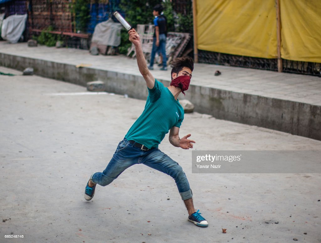 A masked Kashmiri Muslim protester throws teargas shell at Indian government forces during an anti India protest on May 19, 2017 in Srinagar, the summer capital of Indian administered Kashmir, India. Indian government forces used teargas shells to disperse dozens of Kashmiri Muslim protesters who were throwing stones at them during an anti Indian protest in the Old City of Srinagar, after Friday prayers.