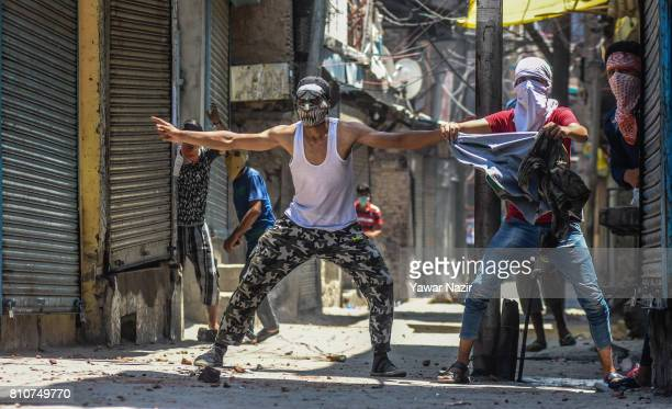 Masked Kashmiri Muslim protesters taunts Indian government forces during a protest after they defied curfew on the the first death anniversary of...