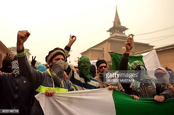 TOPSHOT Masked Kashmiri protestors chant slogans and hold banners and flags during clashes with Indian government forces after the Friday prayer in...