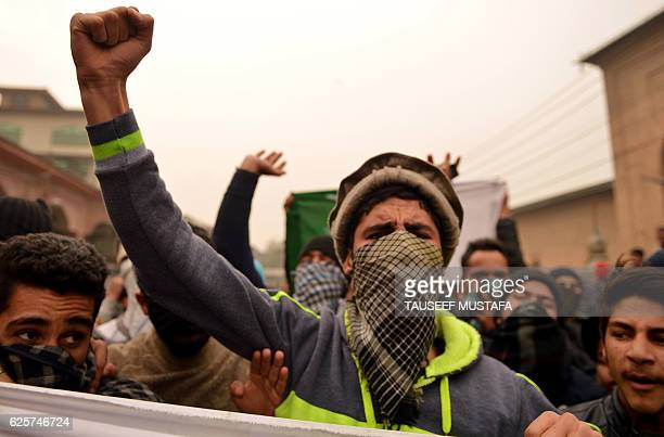 Masked Kashmiri protestors chant slogans and hold banners and flags during clashes with Indian government forces after the Friday prayer in Jamia...