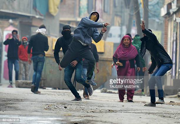 Masked Kashmiri protestors throw stones towards Indian government forces during clashes at a protest against civilian killings in Kashmir's ongoing...