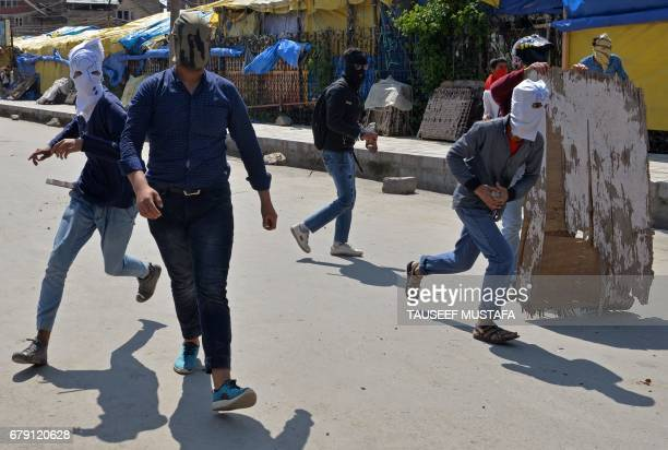 Masked Kashmiri protestors throw stones towards Indian government forces during clashes after Friday congregational prayers outside The Jamia Masjid...