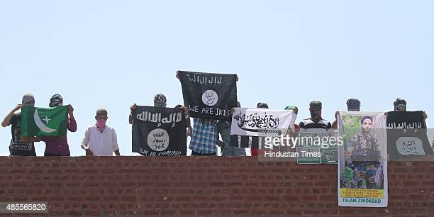 Masked Kashmiri youth hold ISIS LashkareTaiba flags and posters of Pakistan founder Mohammad Ali Jinnah and former ISI Chief Hamid and local militant...