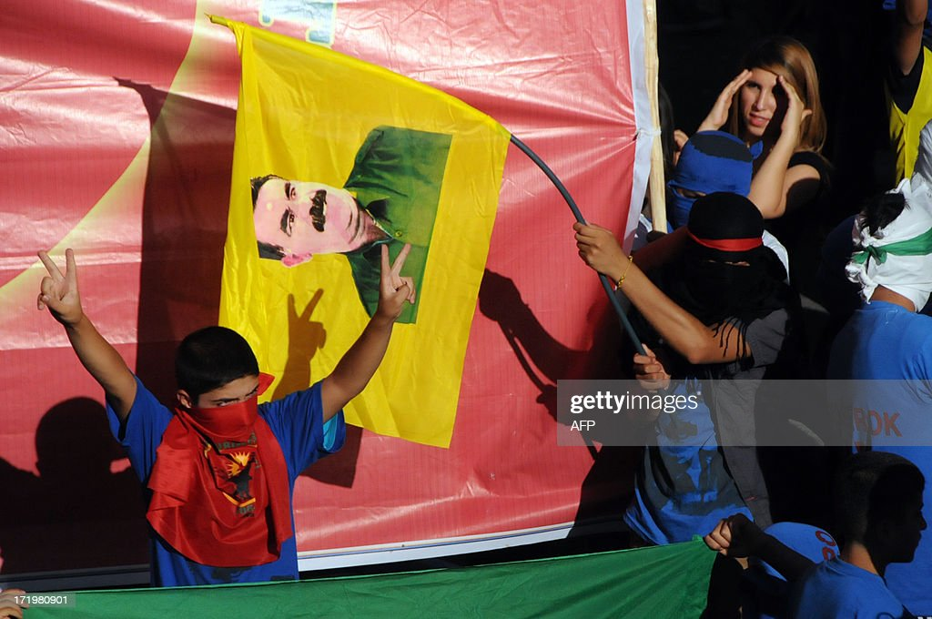 A masked Kurdish boy flahes the 'V for victory' sign while another holds a flag showing a portrait of PKK (Kurdistan Workers Party) jailed leader Abdullah Ocalan during a protest on June 30, 2013, in Diyarbakir. Turkish security forces killed one person and wounded seven on June 28 when they fired on a group of people protesting against the construction of a new gendarmerie outpost in the Kurdish-dominated southeastern Turkey, security sources said.