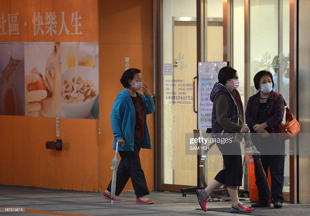 Masked local residents walk past the official Hoping hospital in Taipei on April 24, 2013. International experts probing China's deadly H7N9 bird flu virus said on April 24 it was 'one of the most lethal influenza viruses' seen so far as Taiwan reported the first case outside the mainland. AFP PHOTO / Sam Yeh