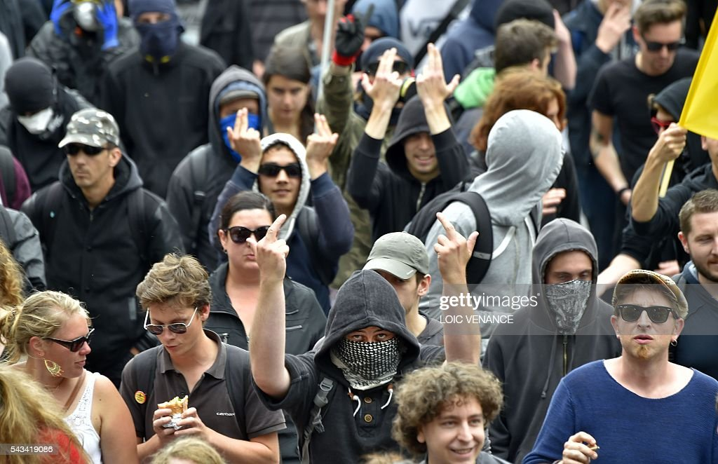 A masked man gives the finger during a protest against controversial labour reforms, on June 28, 2016 in Nantes, western France. People took to the streets in France on June 28 in the latest protest march in a marathon campaign against the French Socialist government's job market reforms. Last month the government used a constitutional manoeuvre to push the bill through the lower house without a vote in the face of opposition from Socialist backbenchers. / AFP / LOIC