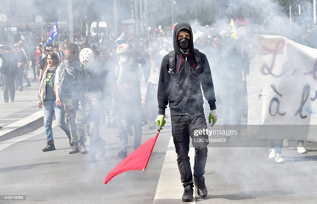 A masked man holds a red flag during a protest against controversial labour reforms, on June 28, 2016 in Nantes, western France. People took to the streets in France on June 28 in the latest protest march in a marathon campaign against the French Socialist government's job market reforms. Last month the government used a constitutional manoeuvre to push the bill through the lower house without a vote in the face of opposition from Socialist backbenchers. / AFP / LOIC