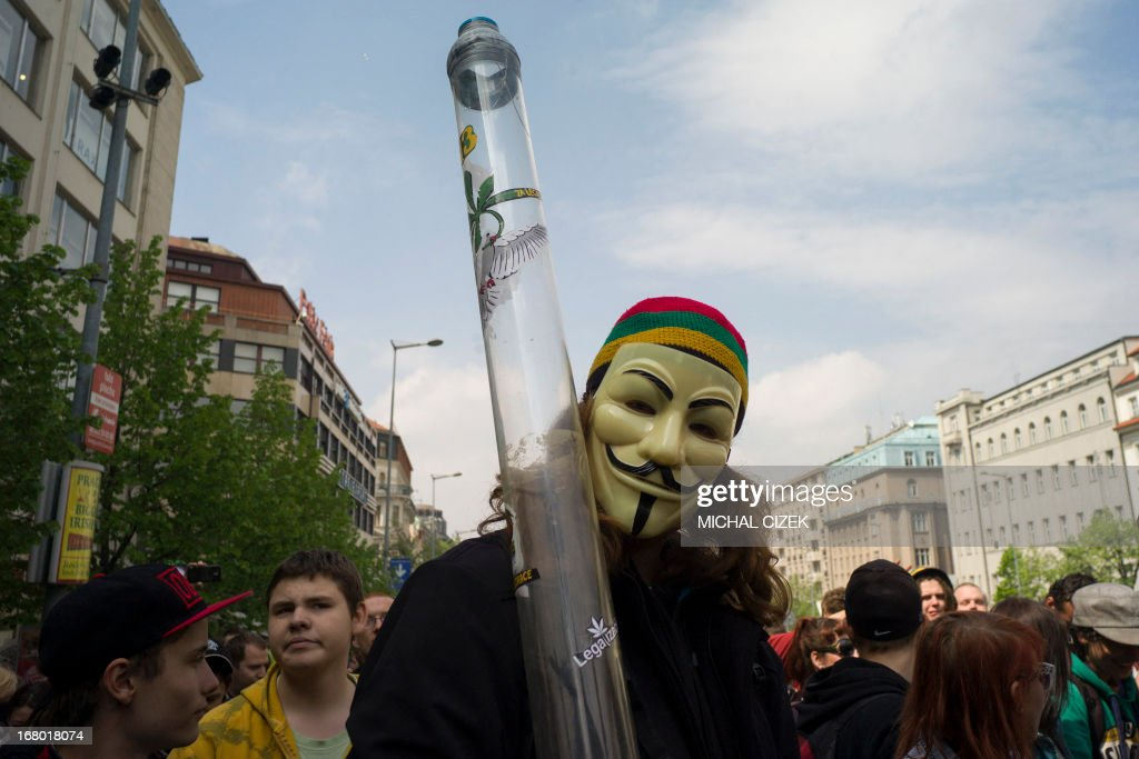 A masked man holds up a water pipe as people take part in a demonstration for the legalization of marijuana on May 4, 2013.