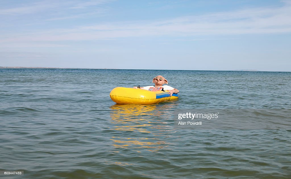 Masked man in blow up boat at sea : Foto stock