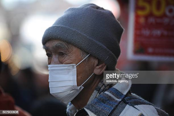 Masked man is seen on the street as japanese people prepare to celebrate the New Year at Yameyokocho and Uechu the most famous and the oldest New...
