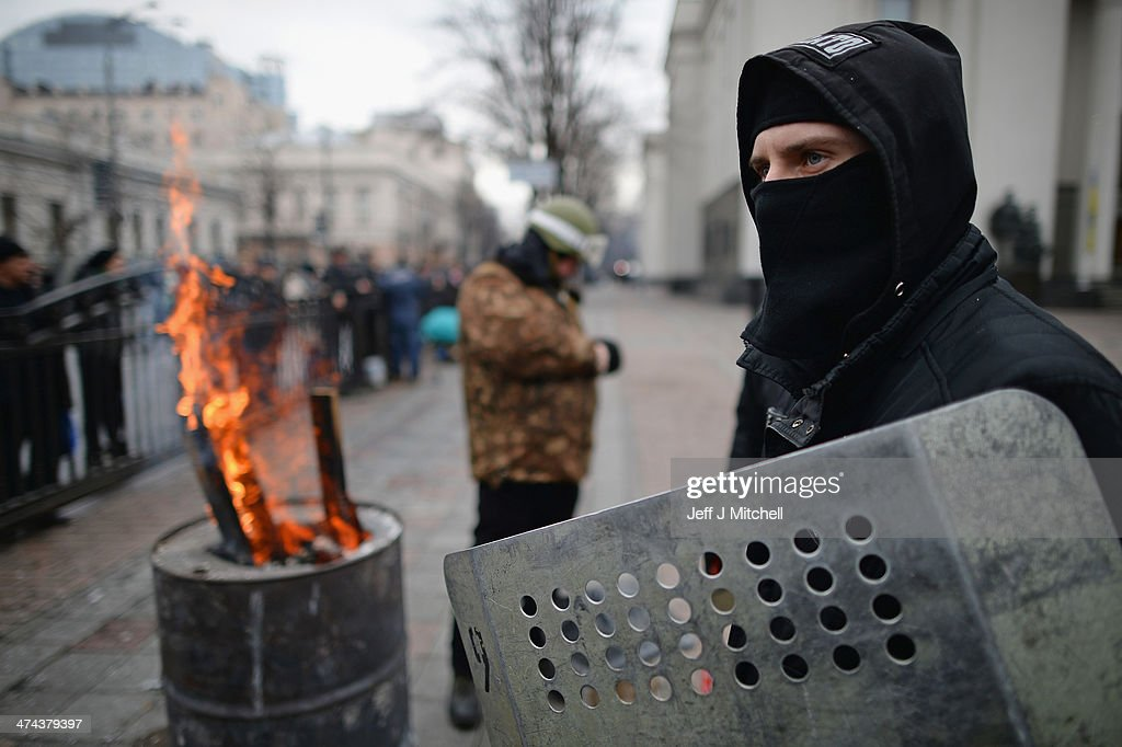 A masked man stands next to a fire outside the Ukrainian Parliament on February 23, 2014 in Kiev, Ukraine. Prime Minister Yanukovych is said to have left Kiev for a eastern stronghold as the country's parliament voted to remove Yanukovych from office and call for new elections.