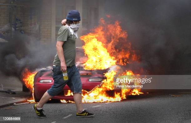 A masked man walks past a burning car outside a Carhartt store in Hackney on August 8 2011 in London England Pockets of rioting and looting continues...