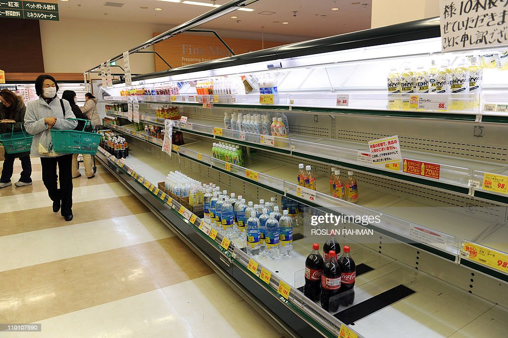 A masked man (L) walks past partly empty shelves as a supermarket runs out supplies of mineral water in the northwestern city of Akita on March 15, 2011 as panic buying sweeps the country following the March 11 earthquake and tsunami in eastern Japan as well as a nuclear crisis in Fukushima prefecture. Japan's nuclear crisis escalated on March 15 as two more blasts and a fire rocked the quake-stricken atomic power plant, sending radiation up to dangerous levels.