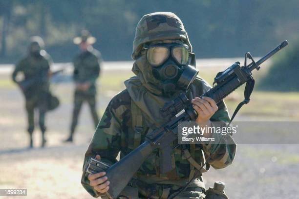 A masked member of Echo Company/1st Batallion/1st Infantry Regiment carries his weapon as he walks back to the rest of his company after practicing...