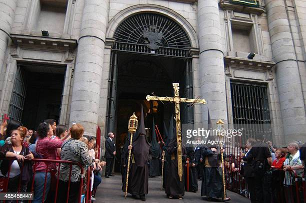 Masked men walk to commemorate the first Christians as Catholics walk during the silence procession of Maundy Thursday in Madrid Spain on April 18...