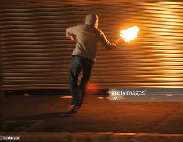 A masked nationalist throws a Molotov cocktail at the police on July 14 2010 during the third night of Nationalist rioting in Belfast The rioting...